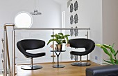 Black, designer easy chairs and side table against glass balustrade of interior staircase