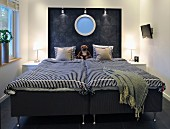 Dark grey double bed with striped cover, porthole with blue glass in charcoal-coloured headboard