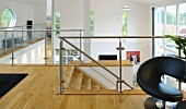 Gallery area with glass balustrade, porthole window and slot-shaped windows in open-plan interior