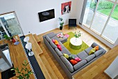 View from gallery down onto grey sofa combination with colourful scatter cushions and green rug surrounded by pale wooden surfaces