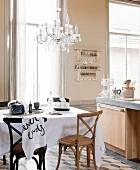 Stühle aus dunklem und hellem Holz an Tisch mit weisser Tischdecke, seitlich moderner Küchenblock in einer Wohnküche