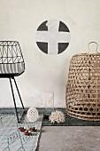 Teilweise sichtbarer schwarzer Metallstuhl und Korb auf verschiedenen, grauen Teppichläufern, an Wand Schablonenmalerei