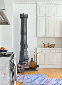 Antique iron stove in white, country-house kitchen with woven rug on plain wooden floor