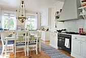 Zentraler, quadratischer Essplatz mit Messingleuchte und gewebte Teppichläufern in geräumiger weißer skandinavischer Landhausküche