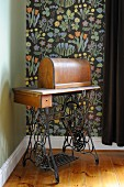 Old pedal sewing machine against floral wallpaper with black background
