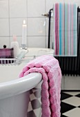 Lilac towel on free-standing bathtub and lit candle on bath rack in background