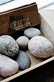 Verschiedengrosse Kieselsteine in Holzbox als Dekoidee