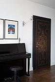 Schwarz lackiertes Klavier und Schemel neben Zimmertür mit Lederbezug und Muster aus Ziernägeln in traditionellem Raum