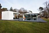 Zeitgenössisches modernes Wohnhaus und Gartenhaus mit überdachter Terrasse am Pool, Bodenplatte aus dunkelgrauen Steinplatten, in freier Landschaft