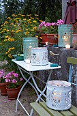 Candles in metal buckets with cut-out designs as lanterns on a table and a chair in a garden