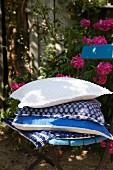A stack of cushions with blue and white covers on a garden chair