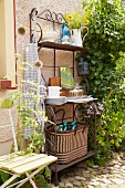 Verschnörkeltes Eisenregal mit Küchenutensilien und Gartenstuhl an Hausfassade