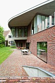Expressionist house with protruding, curved, flat roof, brick lower facade and brick-paved terrace