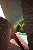Boldly shaped concrete roof over sloping brick path next to polygonal swimming pool