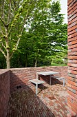Brick terrace with minimalist table-and-bench unit in front of garden with mature trees in spring