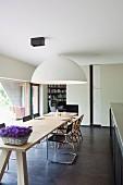 Lange Tafel aus hellem Holz mit klassischen Freischwingern und riesiger Halbkugelleuchte an der Decke in offener Küche