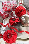 Christmas baubles and gifts on plate in shades of red, silver and white
