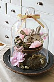 Easter arrangement under glass cover with hand-sewn Easter bunnies, moss and quails' eggs on cake stand
