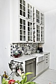 Kitchen counter with traditional, blue and white tiles splashback and white wall units with lattice doors; retro ambiance