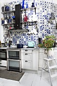 White kitchen counter against wall tiled with traditional, white and blue, country-house-style tiles