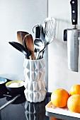 weiße Retro-Blumenvase als Kochlöffel- und Besteckhalter auf schwarzer Granit-Küchenarbeitsplatte
