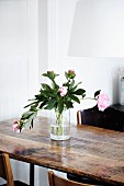 Pink peonies in glass vase on wooden table