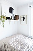 Bed with shiny bedspread below picture and house plant on bracket shelf