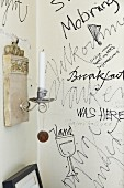 Scribbles and drawings on section of white wall and white candle in candle sconce