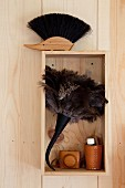 Feather duster and original brush on and in wooden box on pine wall