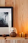Holz-Eulenfigur und Teelicht auf Ablage an Holzwand