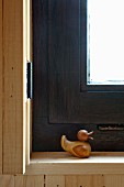 Wooden duck on plain wooden sill of window with black-painted frame