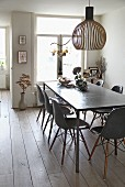 Designer lampshade made from birch above dining table with polished concrete top and shell chairs in dining room