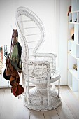 Collection of handbags hanging from white, wicker empress chair next to open-fronted shelving