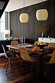 Dark wooden dining table, 60s wicker chairs and pale pendant lamps in front of black wall
