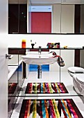 Brightly coloured rug reflected in mirrored wall behind sink and wall-mounted toilet below mirrored cabinet