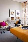 Bilder mit Stiefmütterchenblüten über schmalem Schreibtisch und 60er Jahre Korbstuhl, Doppelbett mit gelber Decke im Schlafzimmer