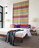 Expressive, colourful zig-zag wall hanging above double bed with brightly coloured pillows and designer pendant lamps