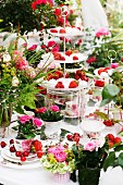 Table decorated with summery arrangement of cake stands, fruit & roses