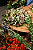 Autumn wreath of sedum, hydrangea & leaves on garden table