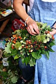 Woman tying wreath of rosehips, acorns, hops & chestnuts
