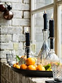 Black candles in round glass bottles standing in dish amongst tangerines