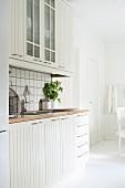 Zeile einer skandinavischen Einbauküche mit weissen profilierten Fronten und Arbeitsplatte aus Holz