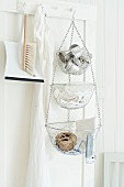 Dustpan and brush and tiered baskets suspended from peg on door in white kitchen