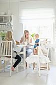 Mutter mit Tochter und Kleinkind im Kinderstuhl an Esstisch in weisser Landhausküche
