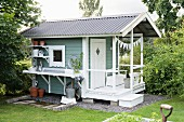 Swedish garden shed with porch and potting table and shelves on one side wall