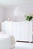 Pendelleuchte mit Tüllschirm und Schubladenschrank vor zart gestreifter Tapete im Schlafzimmer