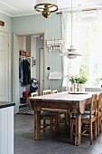 Rustic dining area with solid-wood table and chairs below pendant lamp in country-style kitchen