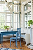 Dining area with blue-painted chair and table in rustic loggia