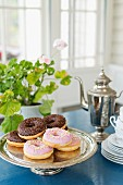 Doughnuts topped with icing and chocolate on silver cake stand