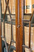 Collection of antiquarian books in glass-fronted cabinet